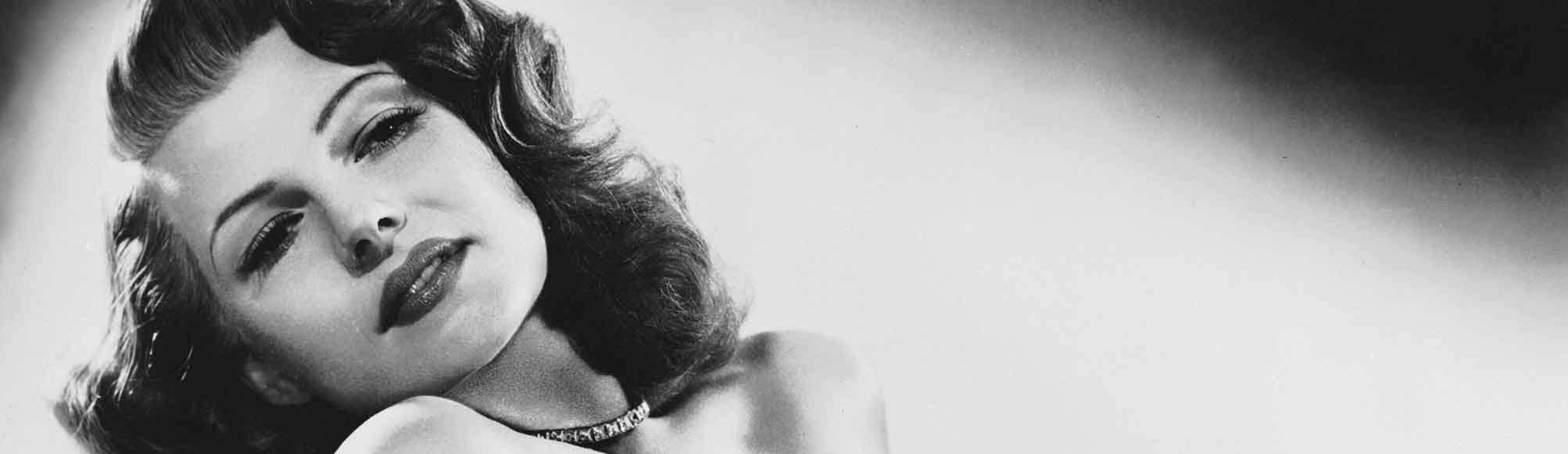 A black and white picture of Rita Hayworth in a black, off the shoulder dress, looking very sultry and glamorous.