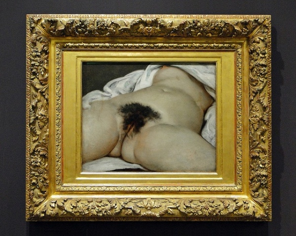 It is a close-up view of the genitals and abdomen of a naked woman, lying on a bed with legs spread. The framing of the nude body, with head, arms and lower legs outside of view, emphasizes the eroticism of the work.