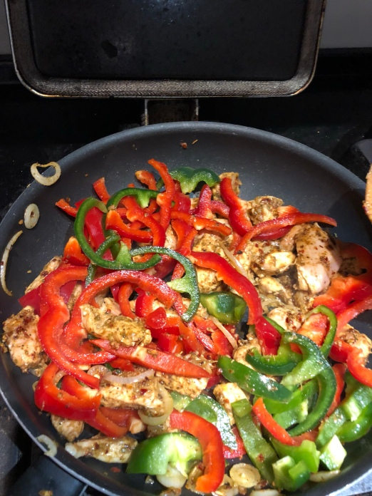 A saucepan on an aga filled with eye poppingly bright red and green peppers in among sliced chicken