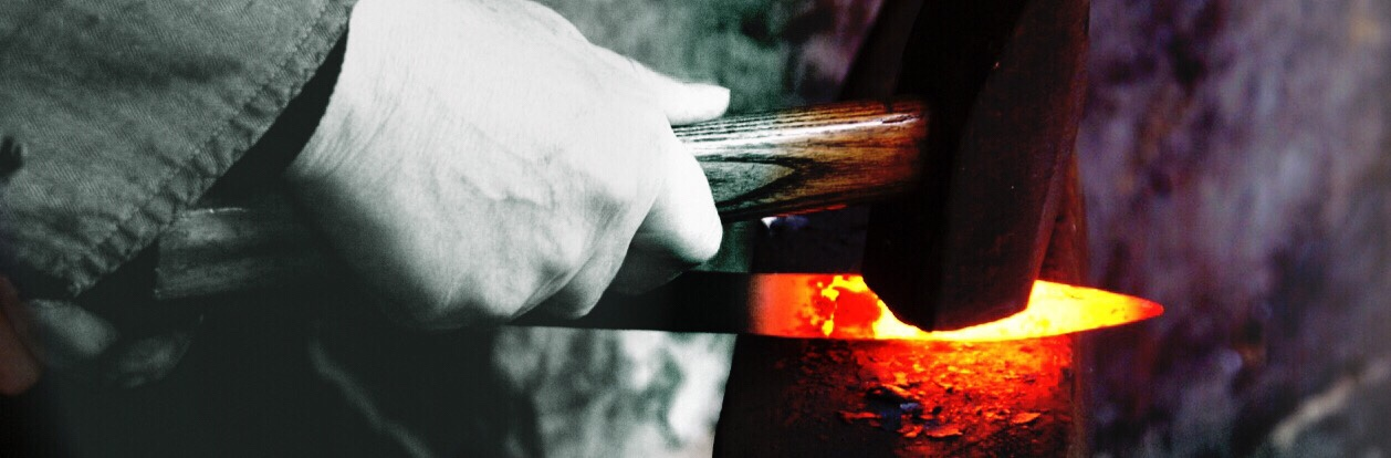 A close up of the hands of a blacksmith. The picture is black and white except for the glowing end of the iron which is rich with reds, oranges and yellows which contrast with the black of the anvil and hammer and the white of the hand. Dramatic and fiery!