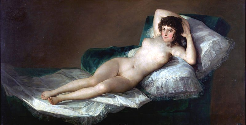 A nude woman reclines on white sheets and pillows with a bold look at the camera. Her legs are together but you can make out a tuft of body hair.