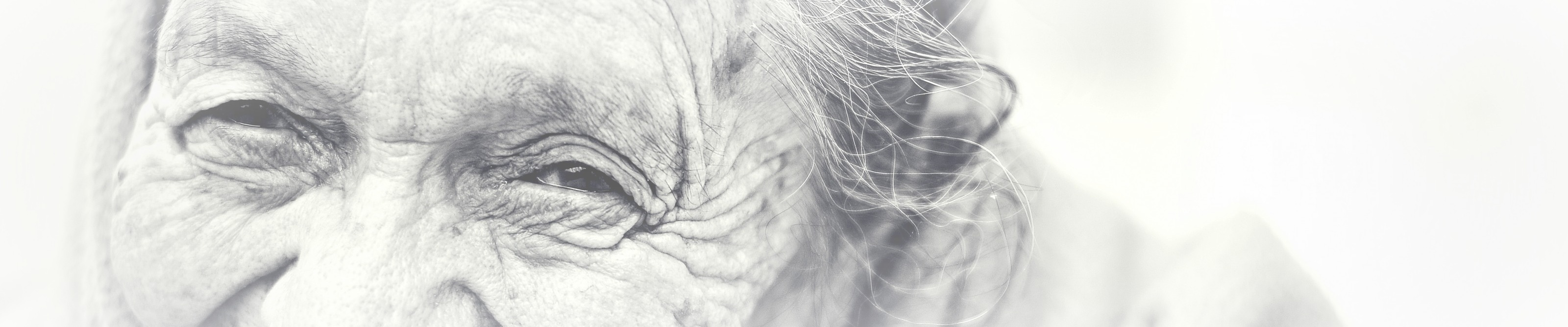 An extremely close up black and white picture of the eyes, forehead and top of noise of a really really old, wrinkly woman. She has a twinkle in her eye and a properly joyful face.