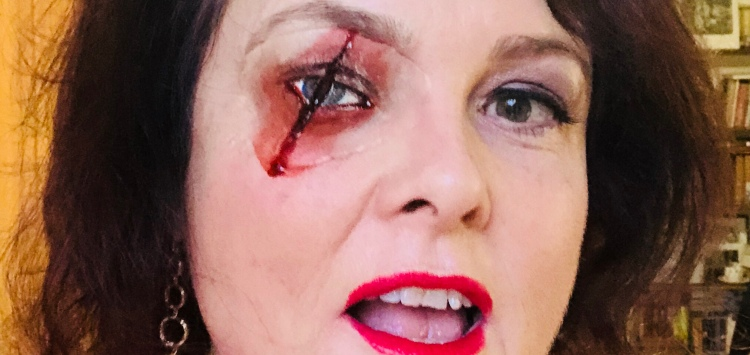 A close up of my face with a fake eye which has been slashed across the middle with blood pouring out