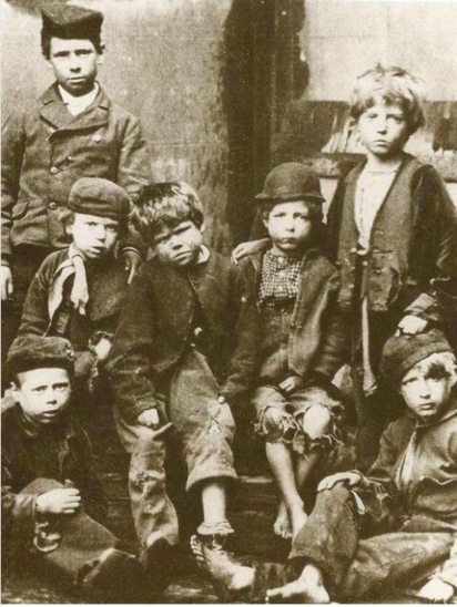 A black and white photo of a group of Victorian Slum children wearing ragged clothes.